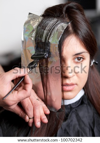 Close up of a hairdresser coloring woman's hair. Selective focus.