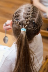 Close-up of a hairstyle with pigtails on the girl's head and a ponytail of hair. Hair styling is done with hairpins and an elastic band. Only the back of the head with a haircut.