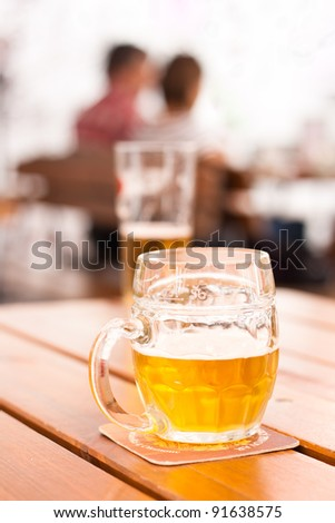 Close-up of a half-filled beer mug on a table in a city restaurant outdoor area