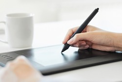Close up of a hand holding a pen and drawing on a tablet surface retouching, drawing or making a graphic design