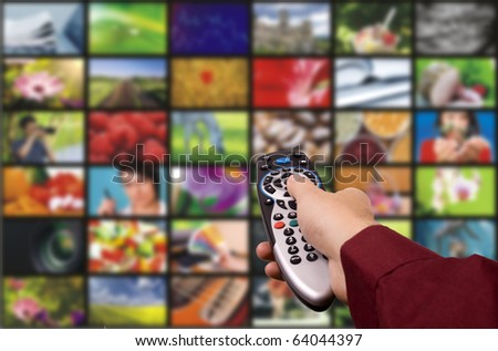 Close up of a hand holding a remote control with a television concept.