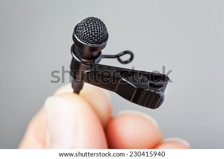 Close-up of a hand holding a tie-clip microphone against a plain background
