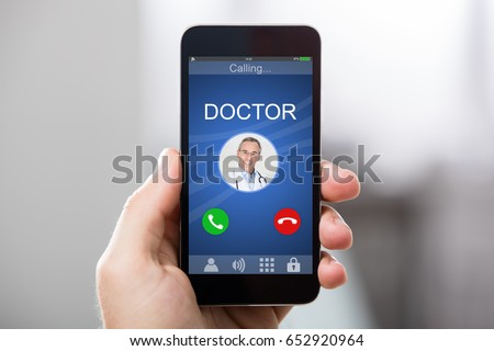 Close-up Of A Hand Holding Smart Phone With Doctor's Incoming Call On Display