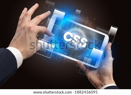 Close-up of a hand holding tablet with CSS abbreviation, modern technology concept Zdjęcia stock ©