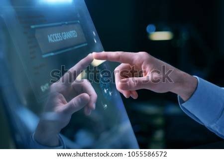 Close up of a hand of a businessman touching a glass monitor in which futuristic graphics appear with the holography. Concept of: future, business, finance, security.