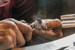 Close-up of a hand of a goldsmith who builds a precious jewel with valuable diamonds. To make the jewel it takes: precision, craftsmanship and patience. Concept of: gold, luxury.