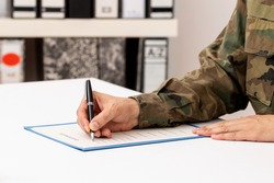 Close up of a hand of a man writing or signing a document on a desk in the military academy
