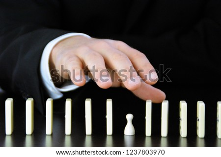 Close-up of a hand of a young businessman examining a disturbance factor in an otherwise perfectly functioning chain reaction from dominoes - symbolic of the complexity of leadership decisions #1237803970