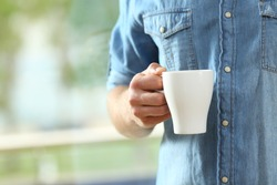Close up of a hand of man holding a coffee cup beside a window with a green background outside