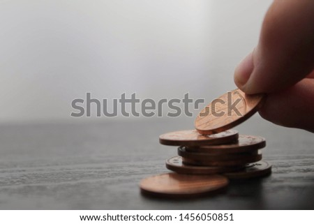 Close up of a hand placing a penny on top of a stack of pennies on a black wooden surface. Savings concept Сток-фото ©
