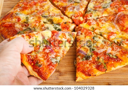 Close-up of a hand taking a slice of homemade pizza