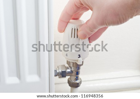 Close up of a hand turning a radiator knob either up or down.  Steel fittings and part of radiator visible, with cream painted wall and skirting board in the background.