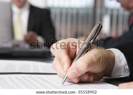 Close up of a hand writing on a document.