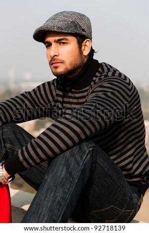 close up of a handsome and confident man wearing sweater and cap in outdoor