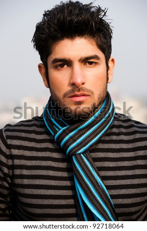 close up of a handsome and confident man wearing sweater and muffler in outdoor