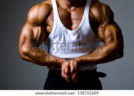 Close up of a handsome man trained bodybuilder standing in a pose with hands joined. Beautiful male body without a head