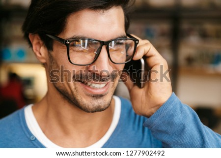 Close up of a handsome young man wearing glasses at the library, talking on mobile phone