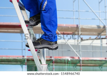 Close-up Of A Handy Repair Man Standing On Steel Ladder Against Construction Sites stock photo