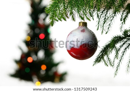 Close up of a hanging red glass ball ornament with blurred Christmas tree on white