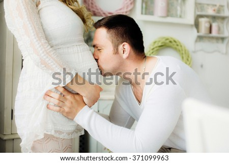 Close up of a happy man kissing the belly of his lovely pregnant wife standing in the white bedroom.  Couple dressed in white clothes. Dad waits the birth of the baby. Sensual photo.