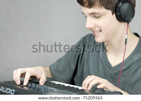 Close-up of a headphone wearing teen adjusting his keyboard.