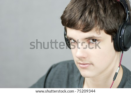 Close-up of a headphone wearing teen looking to camera.