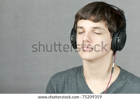 Close-up of a headphone wearing teen meditating.