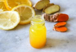 Close up of a healthy Ginger Lemon Turmeric Shot – ideal to boost the immune system during the winter.