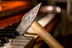 Close up of a heavy hammer banging on keys of a classical piano. Musical ability, style, effort, critics concepts.