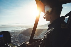 Close up of a helicopter pilot flying aircraft over a city on a sunny day