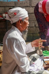 Close up of a Hindu pedanda during prayer. Side view of a sitting priest. Priest holds a bell in his hand and performs the ceremony. Wedding blessing the ceremony.
