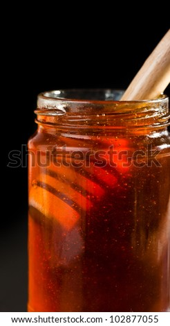 Close up of a honey jar with a honey dipper against a black background