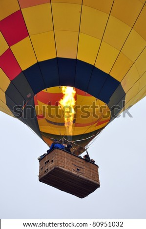 Close up of a hot air balloon in the sky with a basket full of people
