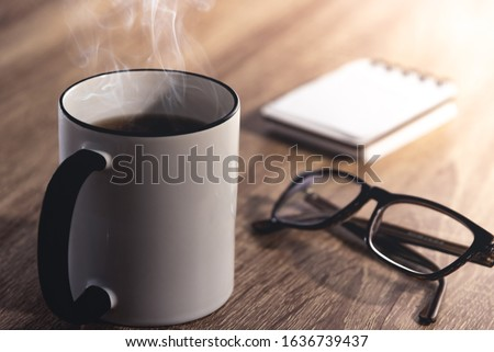 Close up of a hot black and white steaming cup of coffee/tea, modern black glasses and a note book on a wooden desk with intense sun light coming from the side. Relaxation time for drink background. Stock photo ©