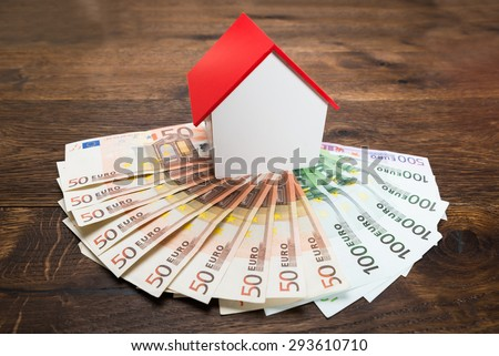 Close-up Of A House Model Kept On Euro Banknotes On Desk