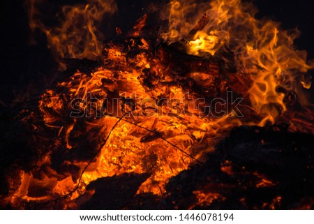 Close up of a huge bonfire with red and orange flames. Intimidating picture.