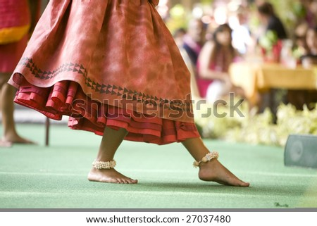 Close up of a hula dancer on a stage, focus on the her feet.
