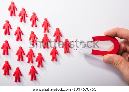Close-up Of A Human Hand Attracting Red Human Figures With Horseshoe Magnet On White Background