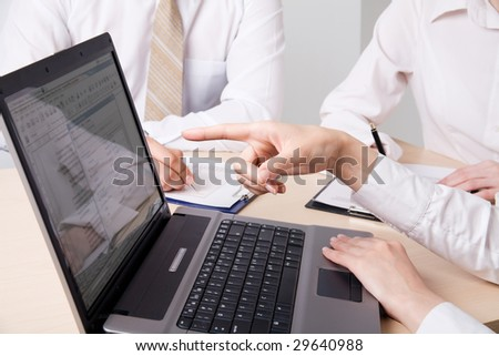 Close-up of a human hand pointing at laptop screen