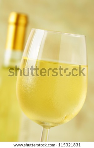 Close-up of a ice cold glass of white wine covered with water drops - condensation