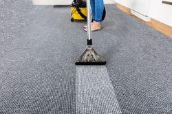 Close-up Of A Janitor Cleaning Carpet With Vacuum Cleaner
