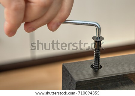 Close-up of a joiner hand with a hexagonal key, screwing a furniture screw into a wooden plank.