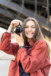 Close up of a jolly young woman holding a vintage camera, smiling and looking in the camera, outside