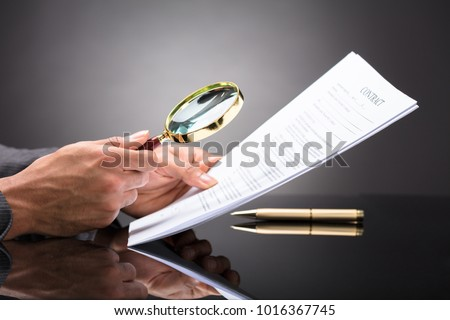 Close-up Of A Judge's Hand Looking At Document With Magnifying Glass