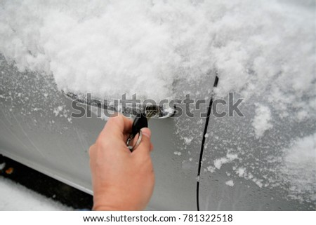Close-up of a key inserted into the lock of frozen car door in winter  #781322518