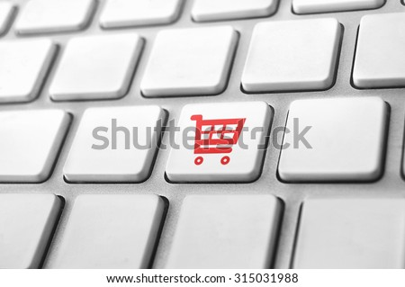 close-up of a keyboard with a shopping cart icon. E-commerce concept