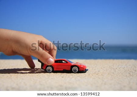 Close-up of a kid hand playing with a racing car