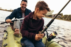 Close up of a kid sitting in a kayak catching fish holding a fishing rod. Happy man rowing a small boat in a lake while his kid tries to catch fish using a fishing rod.