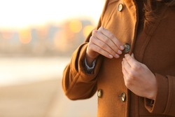 Close up of a lady fastening button of coat on the beach in winter at sunset