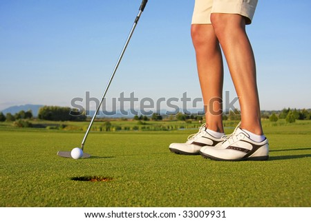 Close up of a lady golfer, putting.